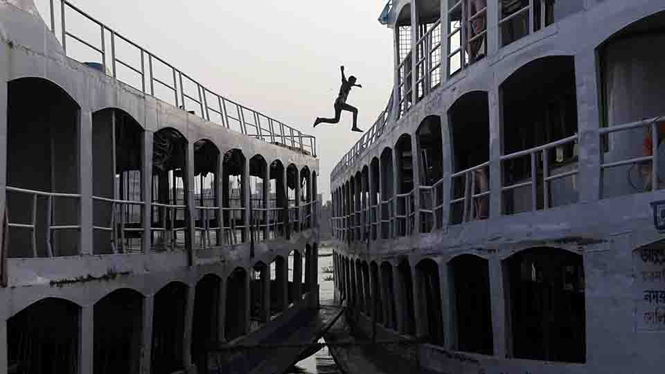 A man jumps from a boat to another by the river Buriganga in Dhaka October 16, 2012.